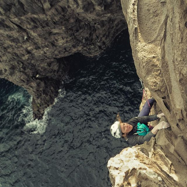 """image: The Caroline Ciavaldini half of @onceuponaclimb topping her route """"Gull,"""" (another Faroese beer!) and...maybe the hardest of the four routes we established here on the #Trælanípa wall.  Hopefully, local or visiting climbers repeat these fun and pumpy... by cedarwright"""