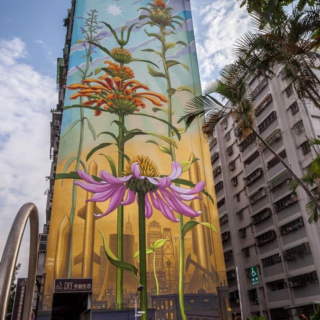 image: Spanning a tower in the Lingya District of the Taiwanese city of Kaohsiung, Mona Caron's mural 'Outgrowing' features medicinal plants from different continents thriving together in a bustling, human-dominated environment to showcase the tenacious power... by saatchigallery