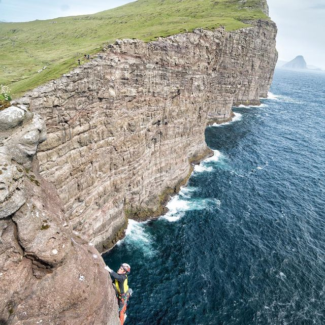 """image: We sent our routes!  Woohoo! Here @onceuponaclimb tops his new 5.12-ish line """"Slupp!"""" ...named after one of  our favorite Faroese beers!  I'm calling my new route Black Sheep after my beer of choice.  This cliff is named #Trælanípa aka Slave Mountain... by cedarwright"""