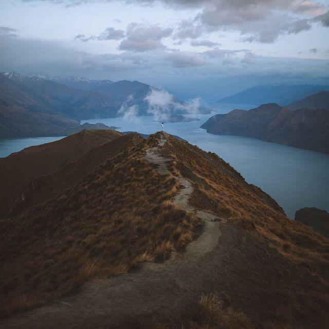 image: Acordamos as 03.45 para fazer uma caminhada de 8km com um desnível de 1km e garantir que víamos o nascer do sol no Roy's Peak. Foi um nascer do sol tímido, choveu toda a noite, mas não podia pedir melhores cores nem melhor vista. by Ventura_Sales